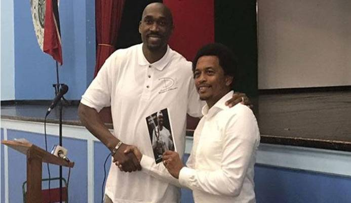 SHARING HIS EXPERIENCE: In this flashback photo, former pro basketballer Kibwe Trim, left, presents a copy of his book to TTOC president Brian Lewis at Trim's alma mater, St Mary's College, in 2017.